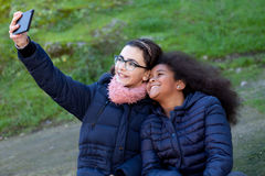 Two girls taking a photo with the mobile Stock Photography
