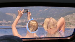 Two girls taking pictures on the phone sitting on. The bow of the boat in Montenegro stock footage