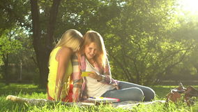 Two girls taking Selfie on green lawn. Young girlfriends on a Picnic on a Lawn, Taking Photos With Mobile Phone, Sitting on a Green Grass in Park. Taking Selfie stock video footage
