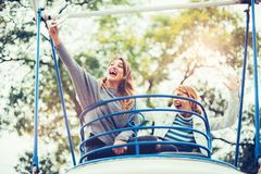 Two girls taking selfie while having fun in amusement park. Two cheerful girls taking selfie while riding on merry go round in amusement park Royalty Free Stock Photo