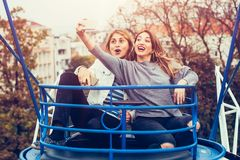 Two girls taking selfie while having fun in amusement park. Two cheerful girls taking selfie while riding on merry go round in amusement park Stock Photography