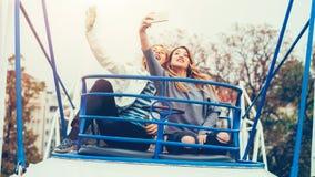 Two girls taking selfie while having fun in amusement park. Two cheerful girls taking selfie while riding on merry go round in amusement park Royalty Free Stock Image