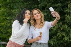 Two girls are taking selfies and eating ice cream royalty free stock image