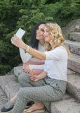 Two girls are taking selfies and eating ice cream royalty free stock images