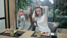 Two girls taking selfies in japanese restaurant. Young girls posing on camera with sushi and mojito in asian restaurant stock video