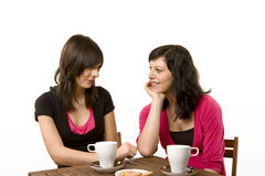 Two girls talk with coffee and cakes Royalty Free Stock Images