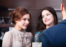 Two girls talk to shop assistant Stock Images