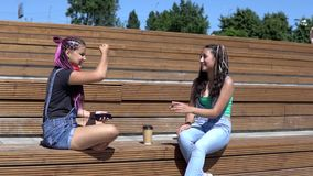 Two girl friends talking to each other having a good mood sitting on a bench in the park. slow motion. Two girls talking on the bench in front of business center stock footage