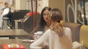 Two girls are talking in a cafe. A conversation between two girls at a table in a coffee shop stock video footage