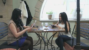 Two girls talking in a cafe and drink coffee. Two stylish girls talking in a cafe and drink coffee stock video footage