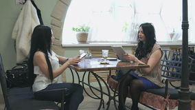 Two girls talking in a cafe and drink coffee stock video