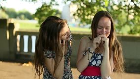 Two  girls talking on cell phone standing in a Park. stock footage