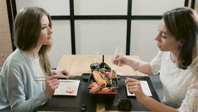 Two girls talking during dinner at the restaurant. Two girls talking in a Japanese restaurant. Two girlfriends  eating rolls and sushi with chopsticks in modern stock video