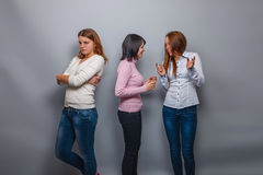 Two girls talking European appearance and ignore. The third girlfriend on a gray background, resentment Royalty Free Stock Image