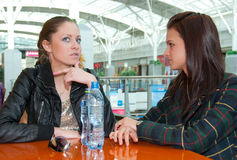 Two girls talking in food court in a mall. Two happy girls drink water and talking in food court in a mall Stock Photos