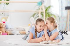 Two girls talking and laughing. Two girls talking, laughing and telling each other secrets in a white room lying down on a carpet Royalty Free Stock Photography