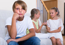 Two girls talking and sulky boy sitting separately at home. Two little girls talking and sulky boy sitting separately at home. Focus on boy Stock Photo
