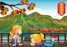 Two girls talking at the wooden bridge. Illustration of the two girls talking at the wooden bridge Royalty Free Stock Images