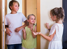 Two girls with teenage boy meeting in doorway Royalty Free Stock Images