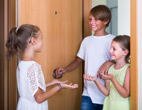 Two girls with teenage boy meeting in doorway Royalty Free Stock Photography