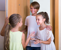 Two girls with teenage boy meeting in doorway Stock Photography