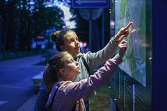 Two girls teenager are looking for the way route on the map scheme at night dark stock photos