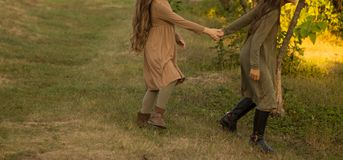 Two girls, teenagers, holding hands, walk on green grass, run in nature. Two girls, teenagers, holding hands, walk on green grass.in a brown and green dress royalty free stock photo