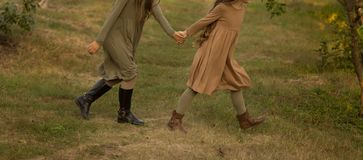 Two girls, teenagers, holding hands, walk on green grass, side view.run in nature. Two girls, teenagers, holding hands, walk on green grass, side view.in a brown stock photos
