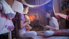 Two girls telling scary stories in tepee tent in bedroom at night stock video footage