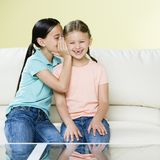 Two girls telling secret on co. Two young girls whispering secret in ear on couch Royalty Free Stock Images