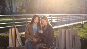 Two girls texting with friends in social network. Two beautiful multiethnic girlfriends sitting on the bench surrounded by many shopping bags texting with stock footage