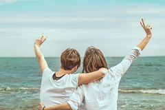 Two girls with their backs to the sea. Feeling of freedom and joy Stock Photo