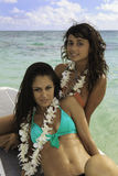 Two girls on their paddle board. Two girls in bikinis and flower lei on their paddle board  in Hawaii Royalty Free Stock Images