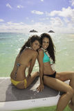 Two girls on their paddle board. Two girls in bikinis and flower lei on their paddle board  in Hawaii Stock Images