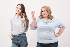 Two girls, thin and fat on a white background, are holding pink glazed donuts in their hands. stock image