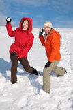 Two girls throw snowballs Stock Images