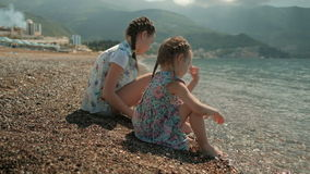 Two girls throw stones in water sitting on beach in summer. Located on coast they take small rocks and throw them happily in warm aqua on sunny day stock video