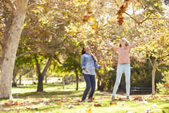 Two Girls Throwing Autumn Leaves In The Air. Having Fun Royalty Free Stock Image