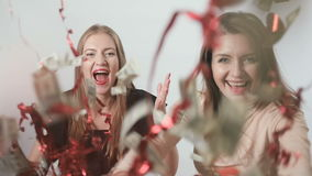 Two girls is throwing forward the dollars with confetti at white background. Two beautiful girlfriends stands in front of camera. Happy young girls is throwing stock video footage
