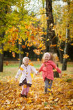 Two girls throwing leaves in autumn park. Vibrant autumn background Stock Photography