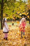 Two girls throwing leaves in autumn park. Vibrant autumn background Royalty Free Stock Image