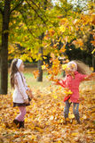 Two girls throwing leaves in autumn park. Vibrant autumn background Stock Photos