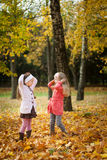 Two girls throwing leaves in autumn park. Vibrant autumn background Royalty Free Stock Images