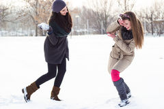 Two girls throwing snow-balls Stock Photos