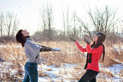 Two girls throwing snow and laughing Stock Photo