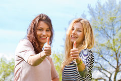 Two girls with thumbs up. Portrait of two girls with thumb up Royalty Free Stock Photography