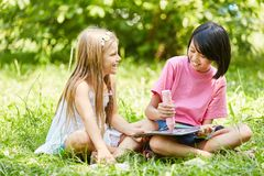 Two girls together paint a picture with chalk. In summer vacations Stock Photos