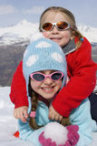 Two girls (6-8) together in snow field, wearing sunglasses, smiling, portrait, mountain range in background Stock Photography