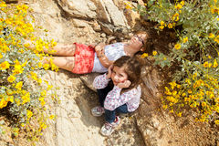 Two Girls Too Tired To Hike. Two sisters rest in the only shade they could find during a hike on a hot, Spring day in Arizona Royalty Free Stock Photography