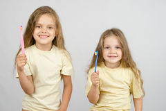 Two girls with toothbrushes Stock Photos